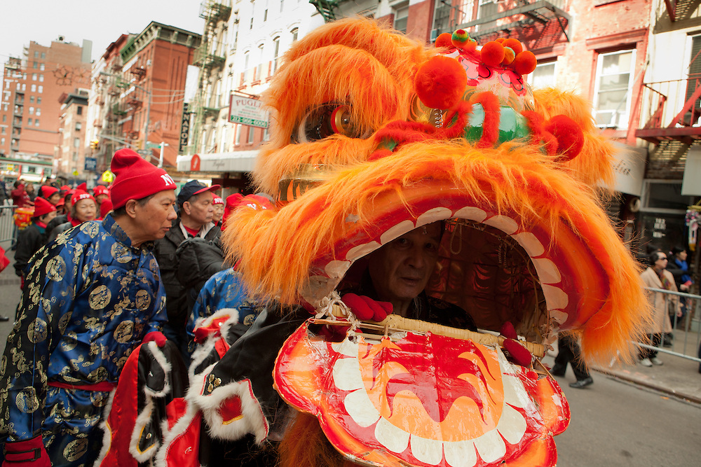 A man in a dragon costume peers from its mouth prior to the start of the Chinese New Year parade.