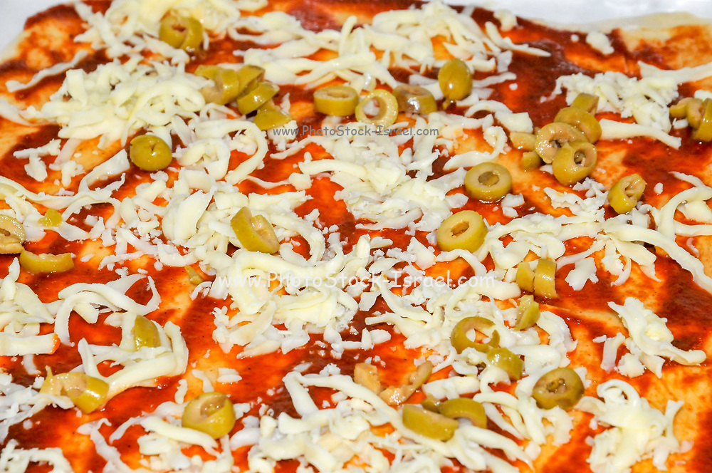 Home made Pizza yellow cheese and olives are placed on the tomato sauce