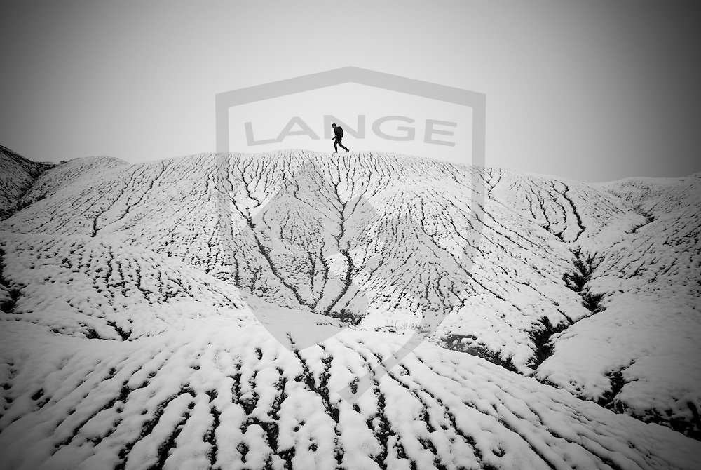 man hiking the snow covered badlands landscape of san ysidro, new mexico.