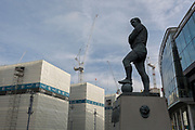 A landscape of regeneration around the Wembley Stadium arena where new properties are under construction tower over the statue of English football's most loved player, Bobby Moore, on 6th November 2019, in Wembley, London, England. Sir Bobby Moore captained England to its World Cup victory against Germany at the old Wembley stadium in 1966.