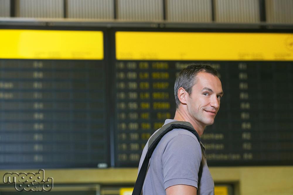 Traveller in front of flight status board in airport