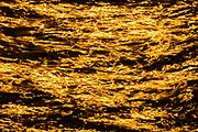 The golden light of the late-day sun streaks across the tops of numerous small Puget Sound waves off of the Edmonds, Washington, shoreline.