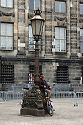 Man on lamp post, in Dam Square, after WW2 Remembrance Day Ceremony in Amsterdam May 4th 2009. The Dutch Queen Beatrix attended, under heavy security and sniper cover following an attempted attack on the Royal Family on Queens Day in Apeldoorn