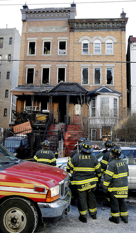Firefighters stand outside of a house where 9 people were killed, 8 of them children, in an overnight fire in the Bronx, New York on Thursday 08 March 2007.