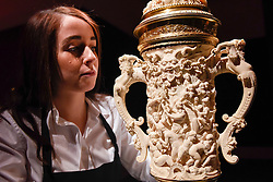 "© Licensed to London News Pictures. 10/02/2017. London, UK.  A technician inspects ""A Two Handled Tankard"" by Neresheimer (est. GBP40-60k), at the preview of the ""Erotic: Passion & Desire"" sale at Sotheby's in New Bond Street.  The sale, which will take place on 16 February, encompasses representations of love and sex from antiquity to the present day.  Photo credit : Stephen Chung/LNP"