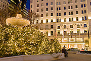 Christmas lights adorn the Pulitzer Fountain in Grand Army Plaza at 59th Street and Fifth Avenue in front of The Plaza Hotel during Christmas season, New York City.