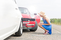 Full-length side view of tensed woman looking at damaged cars on road