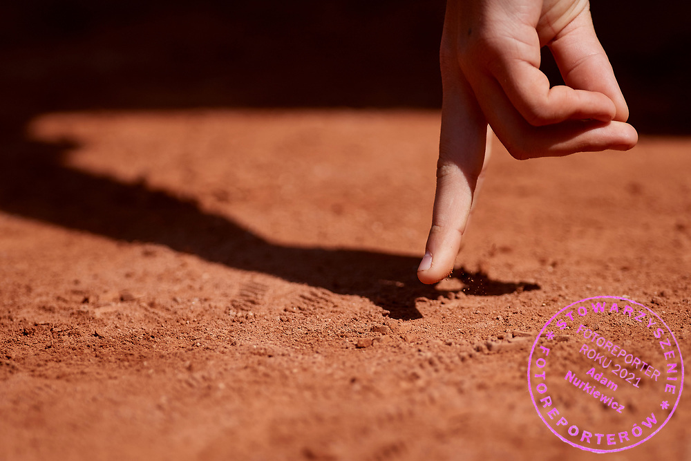 Paris, France - 2017 May 31: Ball kid touches the clay court during tennis Grand Slam tournament The French Open 2017 (also called Roland Garros) at Stade Roland Garros on May 31, 2017 in Paris, France.<br /> <br /> Mandatory credit:<br /> Photo by &copy; Adam Nurkiewicz<br /> <br /> Adam Nurkiewicz declares that he has no rights to the image of people at the photographs of his authorship.<br /> <br /> Picture also available in RAW (NEF) or TIFF format on special request.<br /> <br /> Any editorial, commercial or promotional use requires written permission from the author of image.