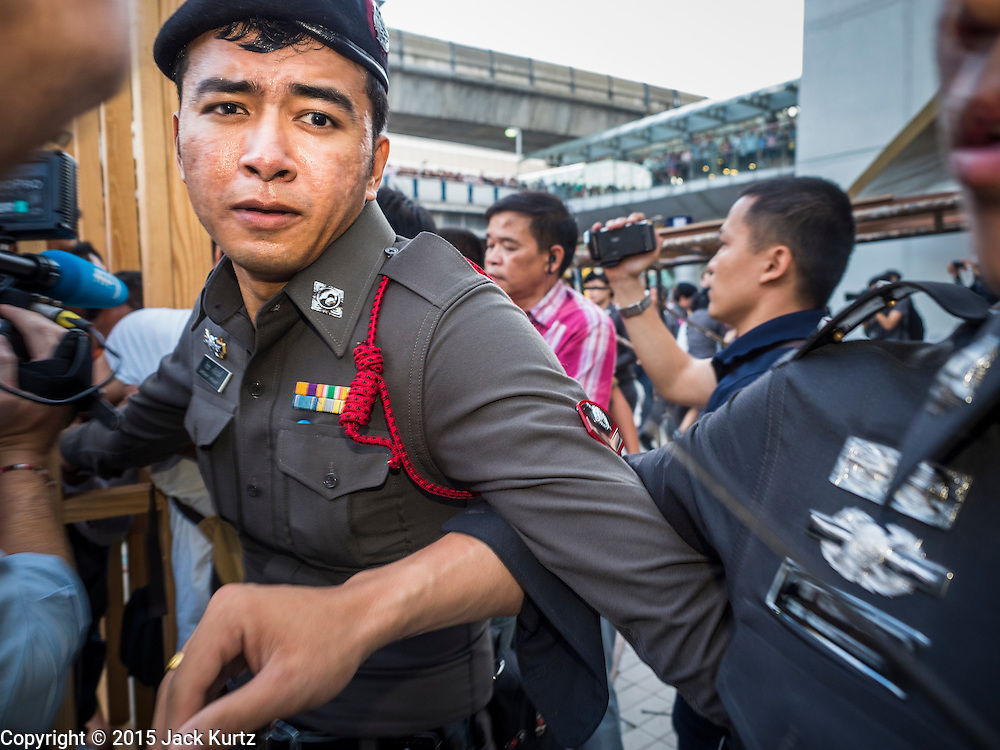 22 MAY 2015 - BANGKOK, THAILAND:  Thai police lock arms during a protest in front of the Bangkok Art and Culture Centre Friday evening. The Thai military seized power in a coup on May 22, 2014. There were small protests throughout Bangkok Friday to mark the first anniversary of the coup. Police arrested protestors at several locations. The most serious protest was at Bangkok Art and Culture Centre (BACC) where about 100 protestors, mostly students, faced off against police for several hours. Police made numerous arrests at the BACC protest.    PHOTO BY JACK KURTZ