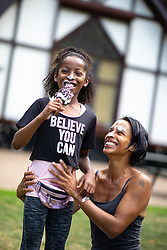 © Licensed to London News Pictures . 26/07/2018. Manchester , UK . ITALEE ANDERSON (eight, correct, from Moss Side) and he mother PAULA ANDERSON (42) share an Oreo Ice Cream in Alexandra Park . People enjoy the summer sunshine in Manchester as temperatures in the UK are forecast to break records . Photo credit : Joel Goodman/LNP