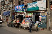 Shopkeepers work on the shop, Kaifeng, Henan, China. 2008