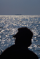 Silhoutte of fisherman with ocean going freighter on horizon background.