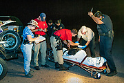 15 JULY 2003 - SELLS, AZ: Tohono O'odham reservation police officers and US Border Patrol agents (red tee shirts)  process the bodies of undocumented immigrants found in the desert southeast of Sells, the capitol of the Tohono O'odham reservation, near Tucson, AZ. Six immigrants were found dead in the desert in one day.    PHOTO BY JACK KURTZ