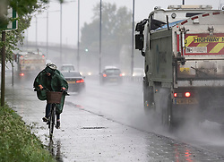 © Licensed to London News Pictures. 28/04/2020. London, UK. A woman riding a bike attempts to shelter form water being sprayed by a passing lorry, during a heavy downpour on the A40 at Perivale in West London. The public have been told they can only leave their homes when absolutely essential, in an attempt to fight the spread of coronavirus COVID-19 disease. British Prime Minister Boris Johnson, who retuned to Downing Street on Monday, has warned the public against relaxing lockdown precautions too soon. Photo credit: Ben Cawthra/LNP