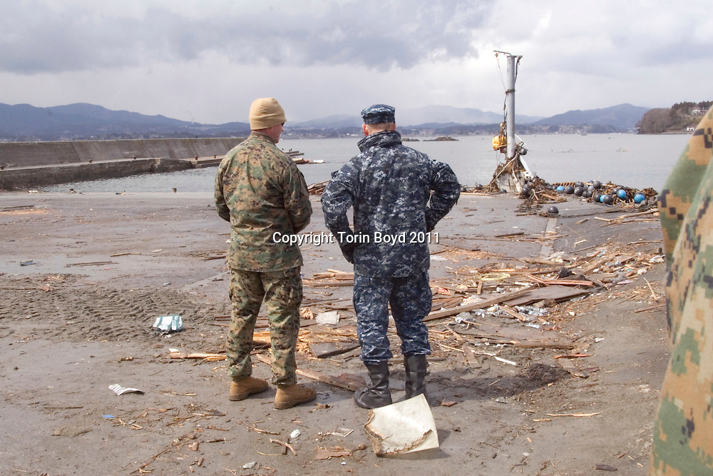 This is US Navy Rear Admiral Scott Jones, Commander Task Force 76.0, meeting with United States Marines from 31st Marine Expeditionary Unit assigned to recovery and cleanup efforts on the hard hit tsunami island of Oshima, in Miyagi Prefecture on April 4, 2011. Jones is seen here in the village of Yogai which was hit by the tsunami that washed over the island. Oshima is an island offshore from Kessennuma City and was devastated by the tsunami caused by the massive 9.0 magnitude earthquake struck Japan on March 11, 2011. Until that time travel to and from the mainland was done via ferry boat service.  With ferry boat service wiped out, all rescue and relief efforts were very slow in coming. That is why the Japan Self Defense Force asked the US military to come to the rescue due to their well equipped amphibious and air capabilities. For the past two weeks 300 Marines have been working on this island around the clock. This is all part of Operation Tomodachi, or Operation Friend which is being coordinated by the US Navy Seventh Fleet.
