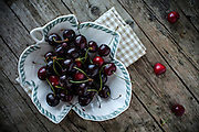 Overhead shot of fresh black cherries in a leaf shaped bowl.