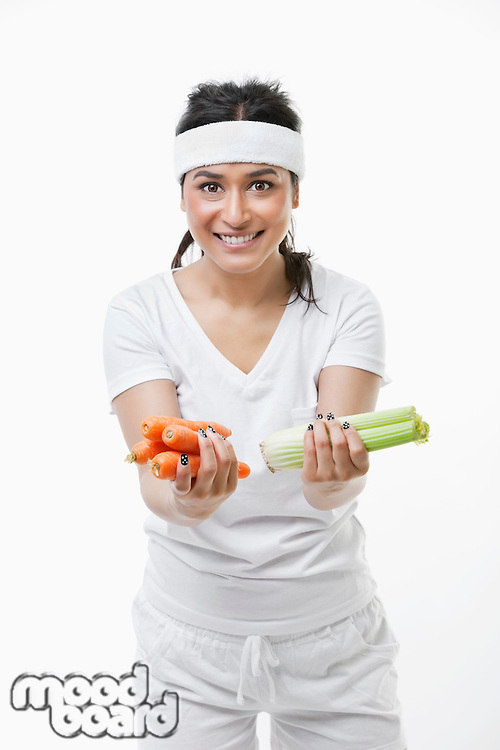 Portrait of young sportswoman holding carrots and celery over white background