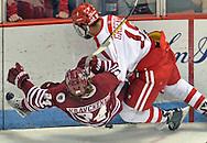 (BOSTON MA 030516)-Boston University's Jordan Greenway sends U Mass' Dennis Kravchenko to the ice as they go into a corner in the third period. Herald photo Chris Christo