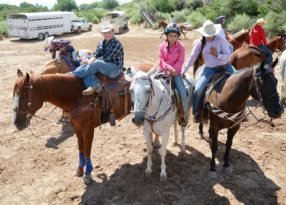 "Elliott Frasier, 12, sits cross-legged on his horse Baw, next to Desirae Limon, 10, center, and Erica Torres, 12, front right, waiting to compete in the pole bending competition during the BernCo Bernie Sheep Day and First Impression Youth Rodeo, Saturday, August 5, 2017, at Bernalillo County's Dennison Park Rodeo Grounds in the South Valley. ""It brings back the western style,"" Frasier said about competing in the rodeo. This is the fourth year for the annual event (Marla Brose/Albuquerque Journal)"