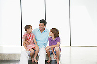 Father with son (7-9) and daughter (5-6) sitting indoors