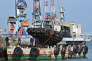 Crane lowers a tugboat into the water. Photographed in the Kishon Harbour, Israel