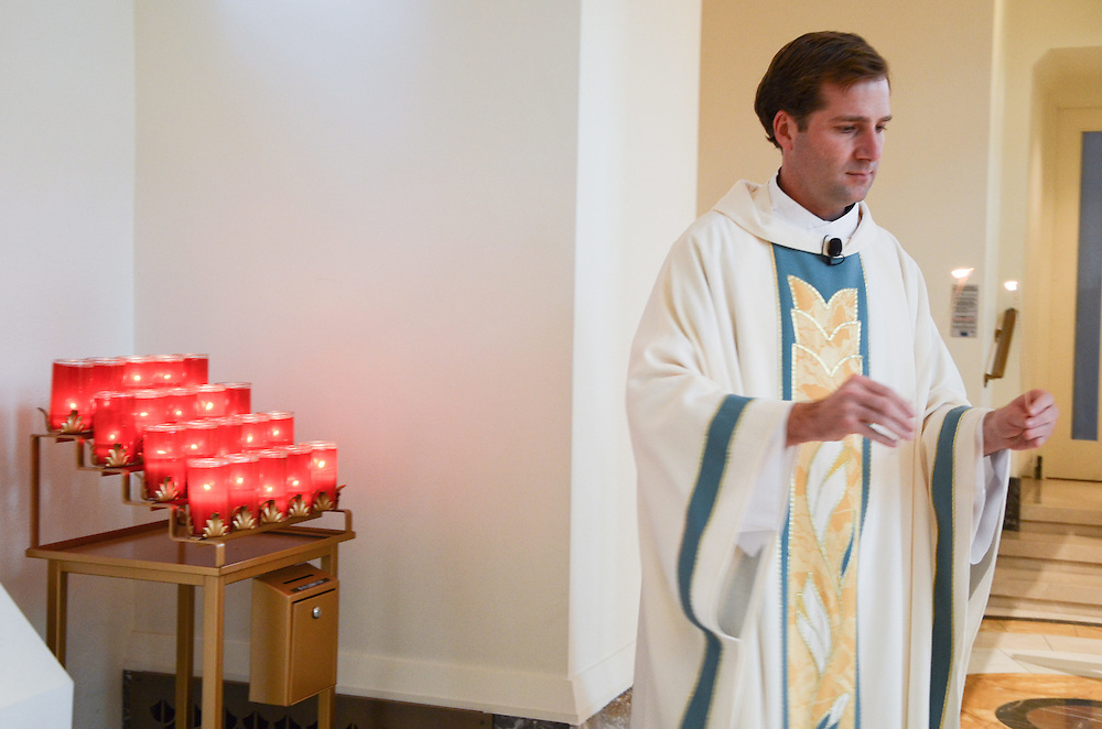 The priest retrieves flames for Kathleen & Brendan's mothers to light the Unity Candle, Madonna della Strada Chapel, Loyola University Chicago