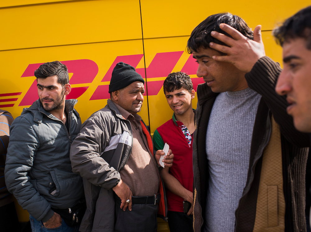 Refugees stand in line at a DHL van to receive documents that have been mailed to them from their native countries - mostly Iraq and Syria - at a refugee camp on the Macedonian (FYROM) border on March 8, 2016 in Idomeni, Greece.