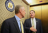 Representative Bruce Braley (D-IA) talks with Representative Tim Murphy (R-PA) in the elevator in Washington, DC on Wednesday, April 10, 2013.
