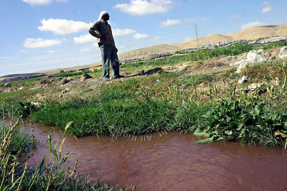 A Bedouin man is walking by an open sewage canal close to one the 45 unrecognised villages of the southern Negev Region of Israel, Gasar Al Sar. Numbering around 200.000 in Israel, the Bedouins constitute the native ethnic group of these areas, they farm, grow wheat, olives and live in complete self sufficiency. Many of them were in these lands long before the Israeli State was created and their traditional lifestyle is now threatened by subtle Governmental policies. The seven Bedouin towns already built are all between the 10 more impoverished towns in Israel..