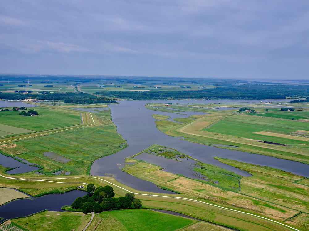 """Nederland, Overijssel, Gemeente Kampen; 21–06-2020; het Reevediep richting monding in het Revemeer (voorheen Drontermeer). Onder de Noordwendigedijk, Flevoland aan de horizon.<br /> Het Reevediep is aangelegd in het kader van het project Ruimte voor de Rivier om bij hoogwater water af te voeren voordat dit het nabij gelegen Kampen bereikt, direct naar het IJsselmeer, de 'bypass Kampen'. Het Reevediepgebied is ook een natuurgebied en vormt een ecologische verbindingszone tussen rivier de IJssel en Drontermeer.<br /> Reevediep towards the mouth in the Revemeer (formerly Drontermeer). On the right the dike Slaper, on the left the Noordwendigedijk, Flevoland on the horizon.<br /> The Reevediep has been constructed as part of the Room for the River project, and functions to discharge high waters before reaching the nearby Kampen, directly to the IJsselmeer, the """"bypass Kampen"""". The Reevediep area is also a nature reserve and forms an ecological connecting zone between the river IJssel and Drontermeer.<br /> <br /> luchtfoto (toeslag op standard tarieven);<br /> aerial photo (additional fee required)<br /> copyright © 2020 foto/photo Siebe Swart"""