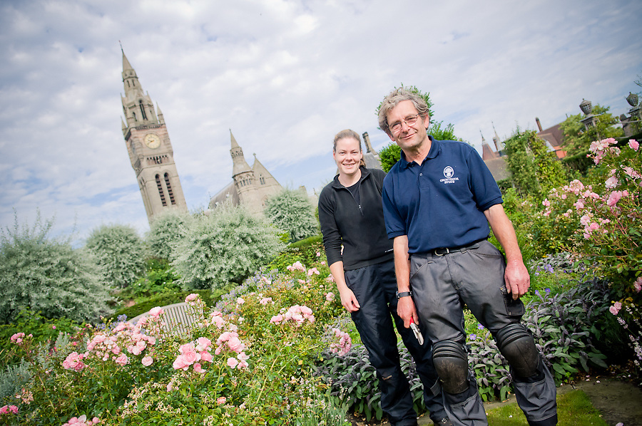 Gardeners standing in eaton estate gardens with eaton hall in the background