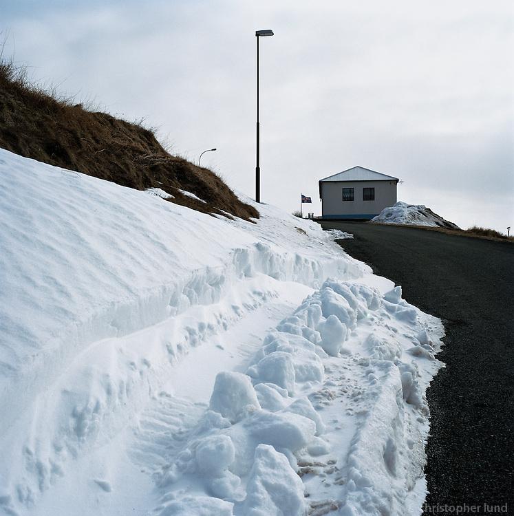Einbýlishús á Hofsós. Snjóskafl í forgrunni. A house at Hofsos, North Iceland. Snow in foreground.