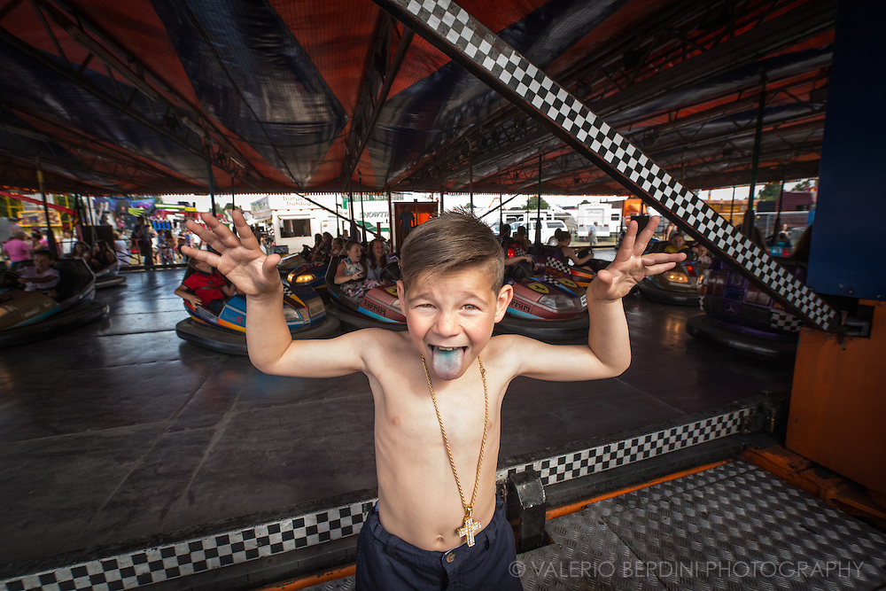 A young boy jokes with his blu tongue in front of one of the fair rides. On the saturday Midsummer Common becomes a amusement park where the youth belonging to the Irish travellers' community enjoys a day out.
