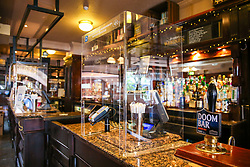 © Licensed to London News Pictures. 03/07/2020. London, UK. A shield around the till in The Toll Gate, a Wetherspoon pub in north London as the pub prepares to reopen on 4 July, the 'Super Saturday'. Pubs across the UK closed on 23 March following the coronavirus lockdown. As COVID-19 lockdown restrictions are eased, pubs will reopen on Saturday 4 July. Some pubs are planning to reopen from 6am. Photo credit: Dinendra Haria/LNP