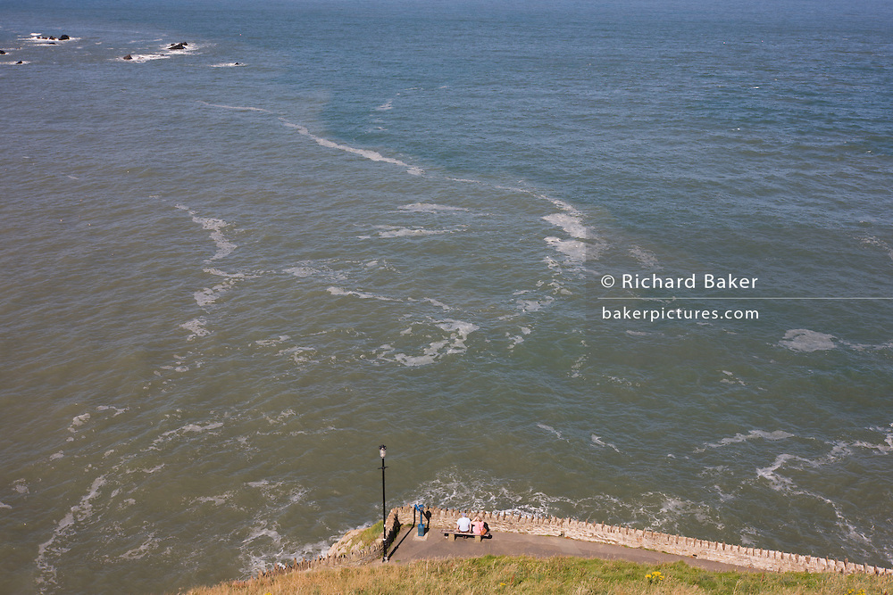 A walking couple rest on a bench at Capstone Hill pverlooking the North Devon Coast waters of Ilfracombe.