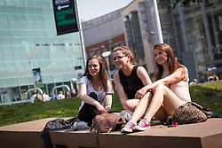 © Licensed to London News Pictures . 05/07/2013 . Manchester , UK . L-R Zoe Lowe (16) , Melissa Ciraki (16)  and Lauren Barnes (15) enjoy the sunshine in Manchester's Cathedral Gardens , in front of the National Football Museum . People enjoy the sunshine in Manchester City Centre . Photo credit : Joel Goodman/LNP
