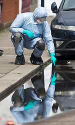 © Licensed to London News Pictures. 03/04/2018. London, UK. A members of a police search team fingertip searching a puddle at the scene on Chalgrove Road, Tottenham, north London where a 17 year old girl was shot dead. The girl was found with a bullet wound and pronounced dead at the scene at 21:43 last night. Photo credit: Ben Cawthra/LNP