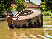 30 SEPTEMBER 2016 - SAI NOI, AYUTTHAYA, THAILAND:  A man in Sai Noi tries to get an empty water storage cistern back to his home. The cistern floated away when the Chao Phraya River flooded Sai Noi. The Chao Phraya River, the largest river that runs through central Thailand, has hit flood stage in several areas in Ayutthaya and Ang Thong provinces. Villages along the river are flooded and farms are losing their crops due to the flood. This is the same area that was devastated by floods in 2011, but the floods this year are not expected to be as severe. The floods are being fed by water released from upstream dams. The water is being released to make room for heavy rains expected in October.     PHOTO BY JACK KURTZ