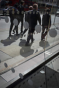 Businessmen pass an office foyer entrance featuring dots and circles (and shadows) on exterior windows in the City of London.