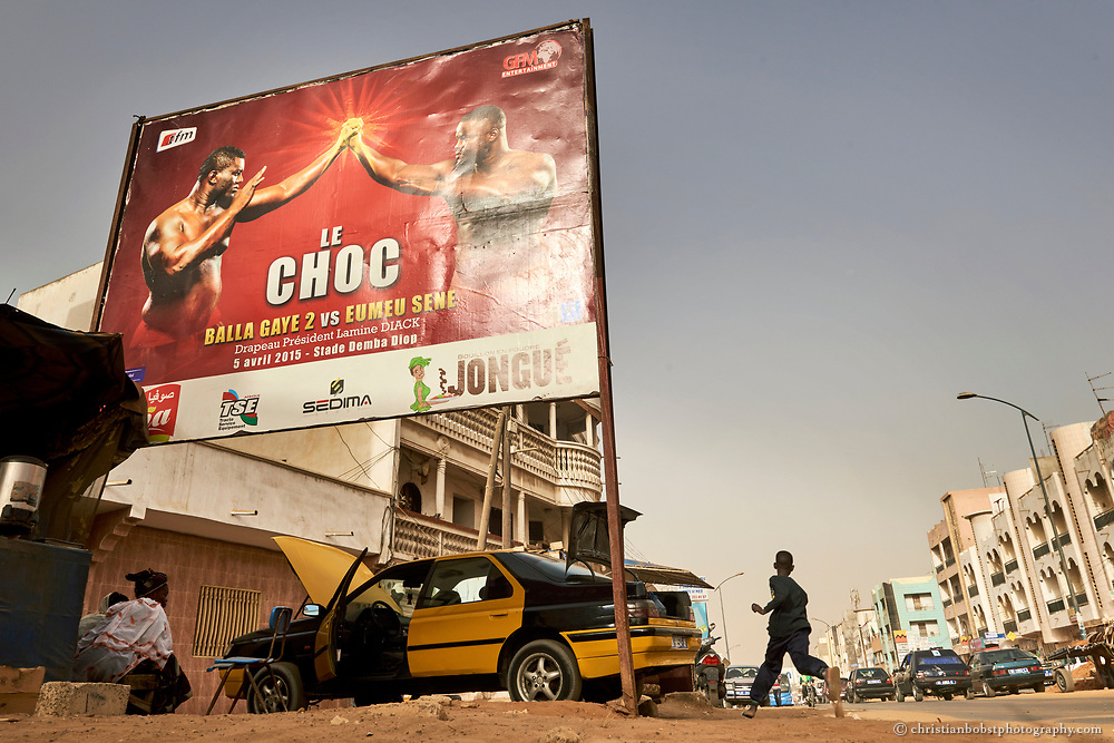 """March 30, 2015. A poster in a street of Dakar advertises a wrestling match between Balla Gaye 2 and Emeu Sene, two superstars of the Senegalese Wrestling. Wrestling (translated into the local language, Woloff, is """"Lamb"""") is the commercially most successful sport in Senegal, even more popular than football."""