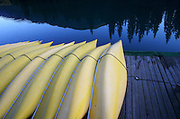 Yellow canoes lined up on dock at dusk, Bow River, Banff Alberta