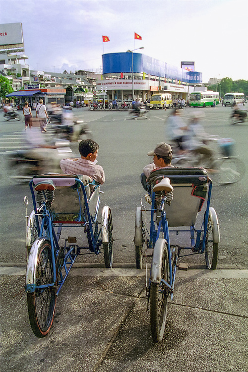 Two rickshaw drivers take a break and are chatting, oblivious to the activity around them. Hô Chi Minh City (Saigon), 2003.