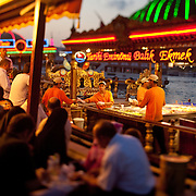 "People dining outside as fish vendors work in the background in Istanbul, Turkey. In the evening in Istanbul, brightly lit fish boats beckon with a promise of a savory treat. For about a century, fishermen have been bringing their catch from the Bosphorus and the Sea of Marmara to Istanbul's Galata Bridge over the Golden Horn for sale. Shouting: ""Balık ekmek! Balık ekmek!"" (Fish in bread! Fish in bread!) a lively scene unfolds bt the water."