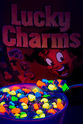 A spoonful of glowing Lucky Charms is lifted from a bowl in front of a cereal box.Black light