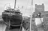Clyde Valley, the former UVF gun-running ship, which is to be towed to a breaker's yard in England, UK. It is seen berthed in the Harbour at Carrickfergus, Co Antrim, N Ireland. Carrickfergus Castle is in the background. 197407300414a <br /> <br /> Copyright Image from Victor Patterson, 54 Dorchester Park, <br /> Belfast, UK, BT9 6RJ<br /> <br /> t1: +44 28 9066 1296 (from Rep of Ireland 048 9066 1296)<br /> t2: +44 28 9002 2446 (from Rep of Ireland 048 9002 2446)<br /> m: +44 7802 353836<br /> <br /> e1: victorpatterson@me.com<br /> e2: victorpatterson@gmail.com<br /> <br /> www.victorpatterson.com<br /> <br /> Please see my Terms and Conditions of Use at www.victorpatterson.com. It is IMPORTANT that you familiarise yourself with them.<br /> <br /> Images used on the Internet must be visibly watermarked i.e. © Victor Patterson within the body of the image and copyright metadata must not be deleted. Images used on the Internet have a size restriction of 4kbs and will be chargeable at current NUJ rates unless agreed otherwise.<br /> <br /> This image is only available for the use of the download recipient i.e. television station, newspaper, magazine, book publisher, etc, and must not be passed on to any third party. It is also downloaded on condition that each and every usage is notified within 7 days to victorpatterson@me.com<br /> <br /> The right of Victor Patterson to be identified as the author is asserted in accordance with The Copyright Designs And Patents Act (1988).