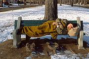 Homeless man age 50 sleeping on park bench.  St Paul Minnesota USA