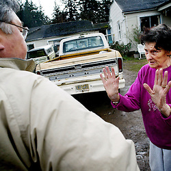 February 28, 2004 - Ann Isaksen, 83 (right), makes a plea to Victor Unkow (left) for more time to clean up her property maintenance code violations on her property located at SE 131st and Long in SE Portland. Victor Unkow is one of 10 housing and nuisance inspectors for the City of Porltand, Oregon. Victor was doing a checkback on the code violations and stated that Ann's property looked much better, and that he would work with Ann and give her more time to make sure that she was in compliance with city code. When Victor tells Ann that he will give her the extra time she needs to clean it up, she says: &quot;I can hug you for that, but I know it's against the law.&quot; <br />