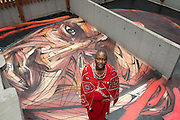 "Masai warrior and representative of the Big Life foundation in Kenya,Daniel Ole Sambu, with the rooftop painting of himself painted by famous Parisian street artist Alexandre Monteiro aka Hopare.<br /> Street art in Hong Kong ahead of the The ""Hope for Wildlife"" Gala Dinner painted to raise awareness for the plight of endangered animals the world over.<br /> 10th November 2016. Photo by Jayne Russell"