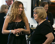 """Kristen Campo, an art consultant at Nan Miller Gallery, speaks with Joan Lissack of Brighton, right, at a ceremony celebrating the installation of Albert Paley's """"Proscenium"""" at Nan Miller Gallery in Pittsford on Tuesday, June 16, 2015."""