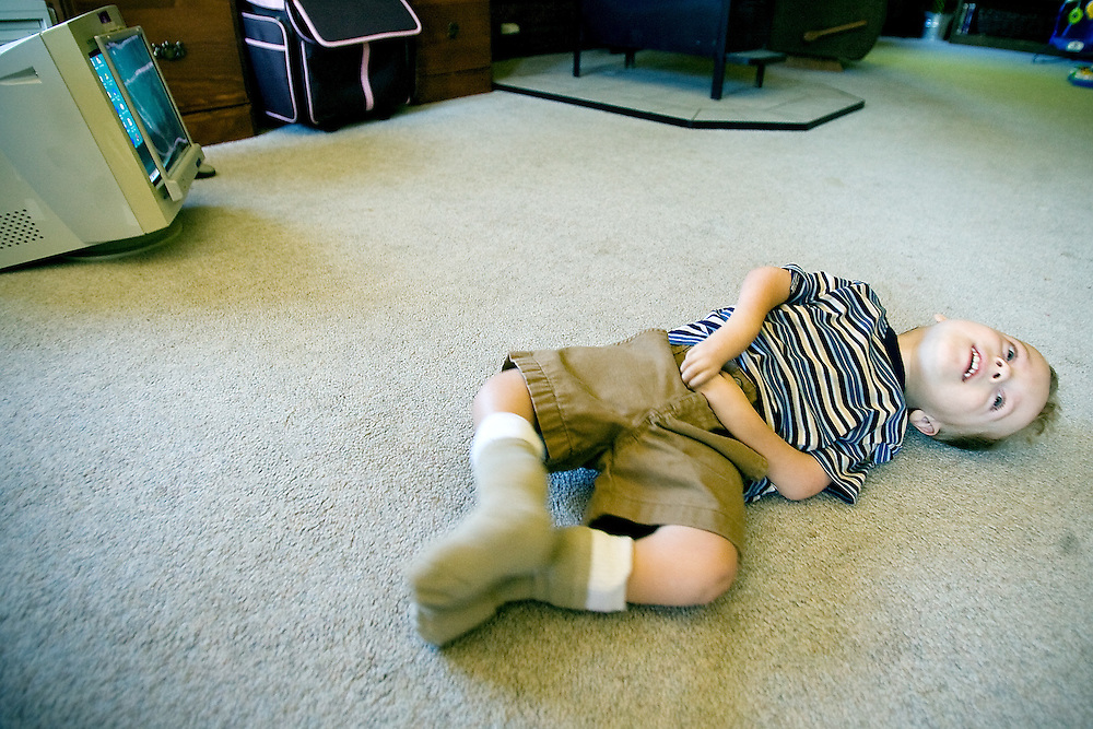 JEROME A. POLLOS/Press..Gavin Scheel, 2, rolls across his living room floor Friday as he makes his way toward the front door. Scheel has limited use of his arms and legs due to a rare congenital disorder and rolls on the floor to get from place to place.